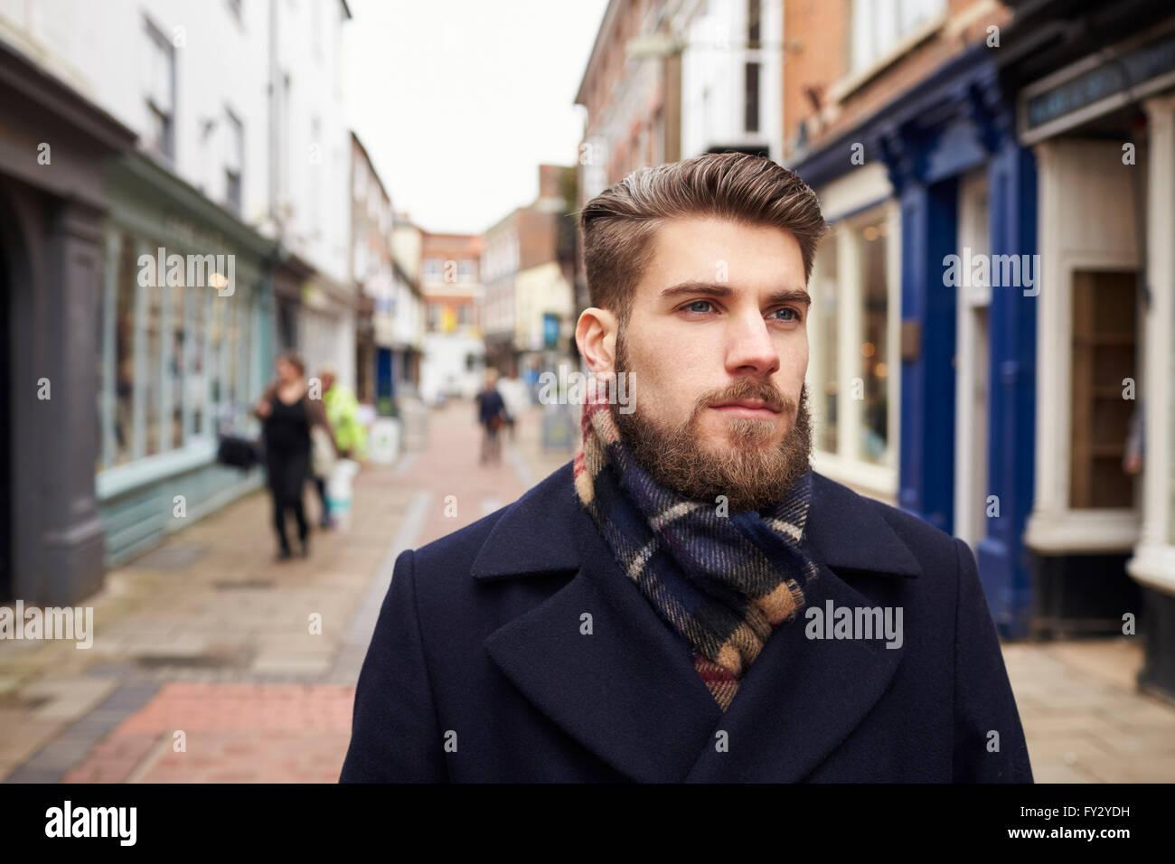 Young Man Walking Down Urban Street - Stock Image