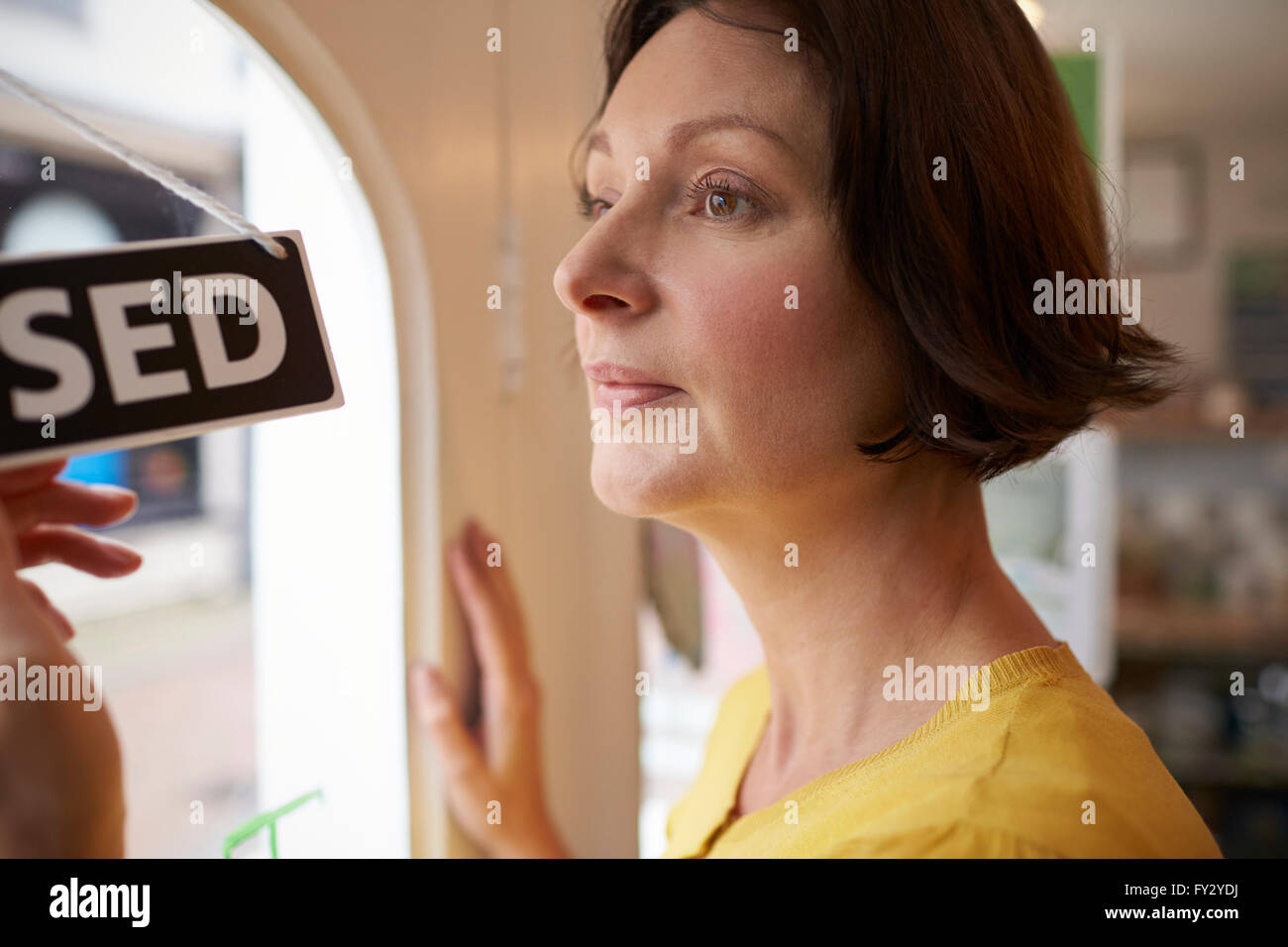 Female Owner Of Coffee Shop Turning Open Sign - Stock Image