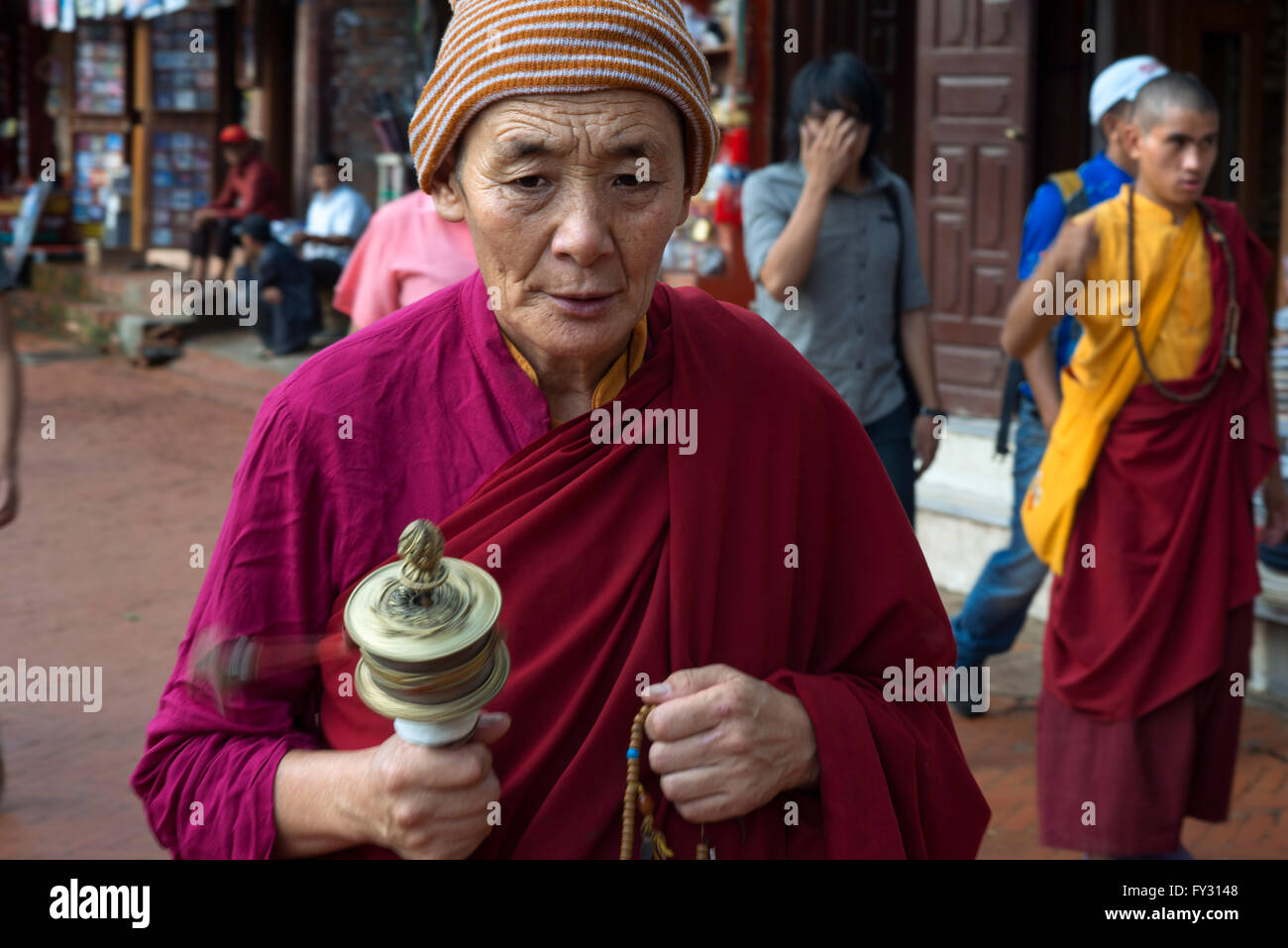 Man with a prayer mill at Boudhanath Stupa, Kathmandu, Nepal. Prayer mill, Bodhnath Stupa, Kathmandu, Nepal, Asia Stock Photo