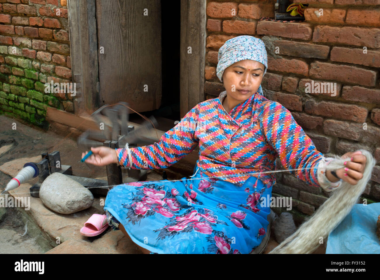 A woman spins wool at the small village of Bungamati, Nepal - Stock Image