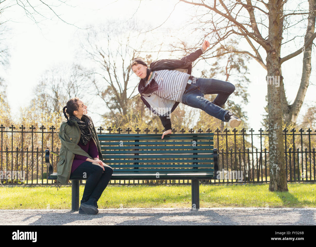 Young man trying to impress indifferent girl by jumping over a park bench, Sweden - Stock Image