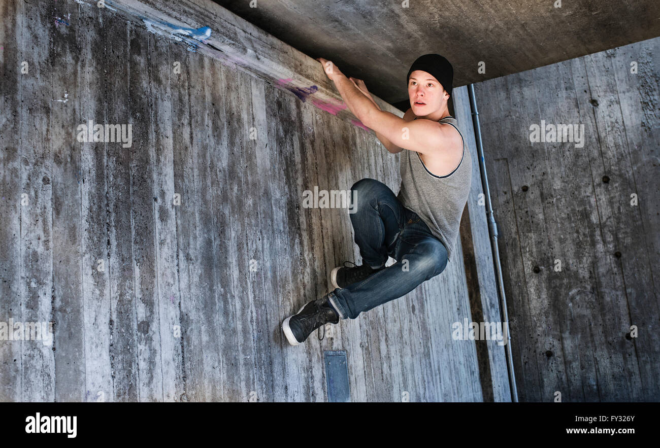 Young man hanging in a parkour move on concrete wall, Sweden - Stock Image