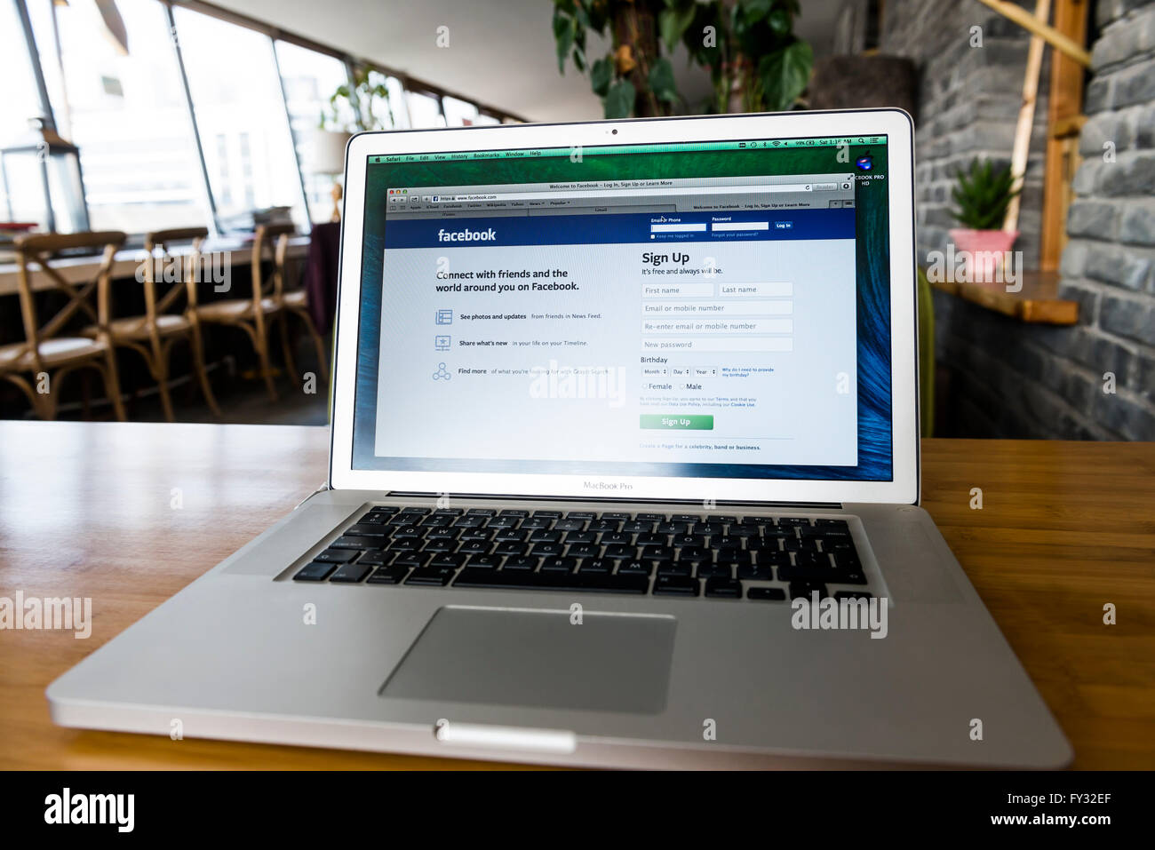 MacBook Pro Apple laptop on a desk with Facebook web page on display - Stock Image
