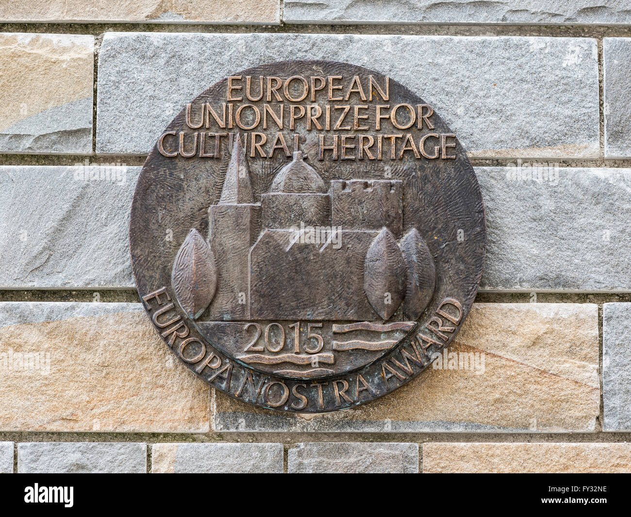 Bronze medallion on stone wall, the European Union Prize 2015 for cultural services and monuments, Aquileia, Udine - Stock Image