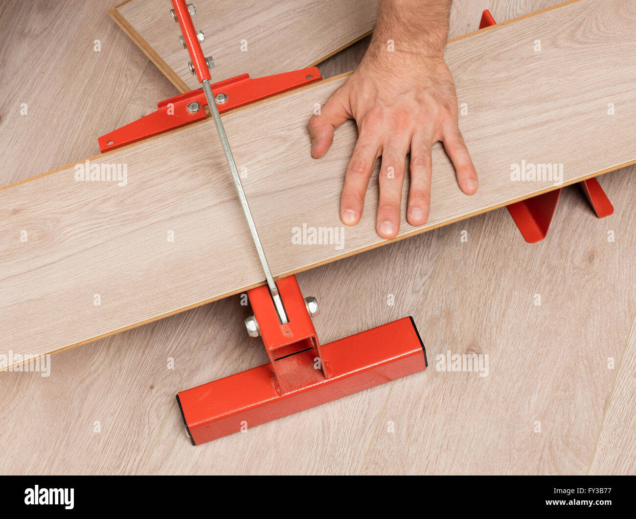 Red tool for cutting laminate on a laminate floor - Stock Image