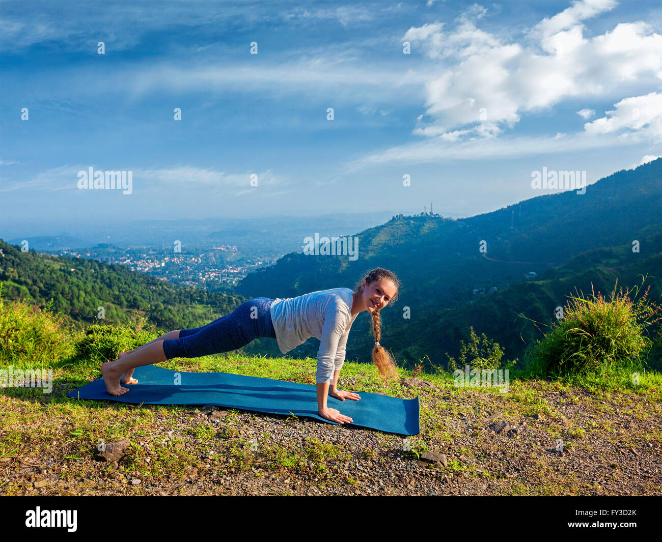 Woman doing Hatha yoga asana plank pose outdoors - Stock Image