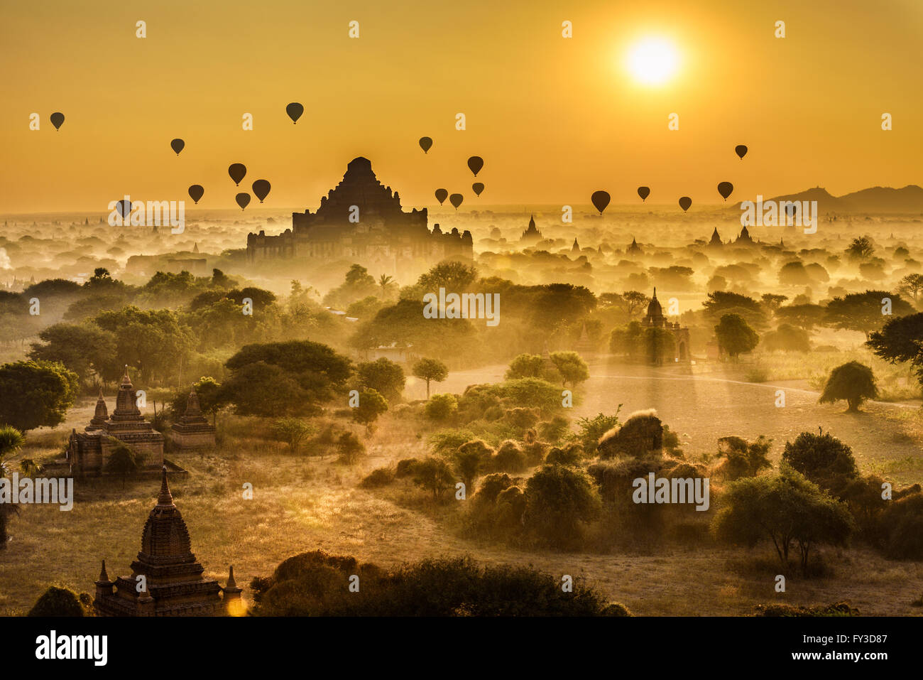 Scenic sunrise with many hot air balloons above Bagan in Myanmar. Bagan is an ancient city with thousands of historic - Stock Image