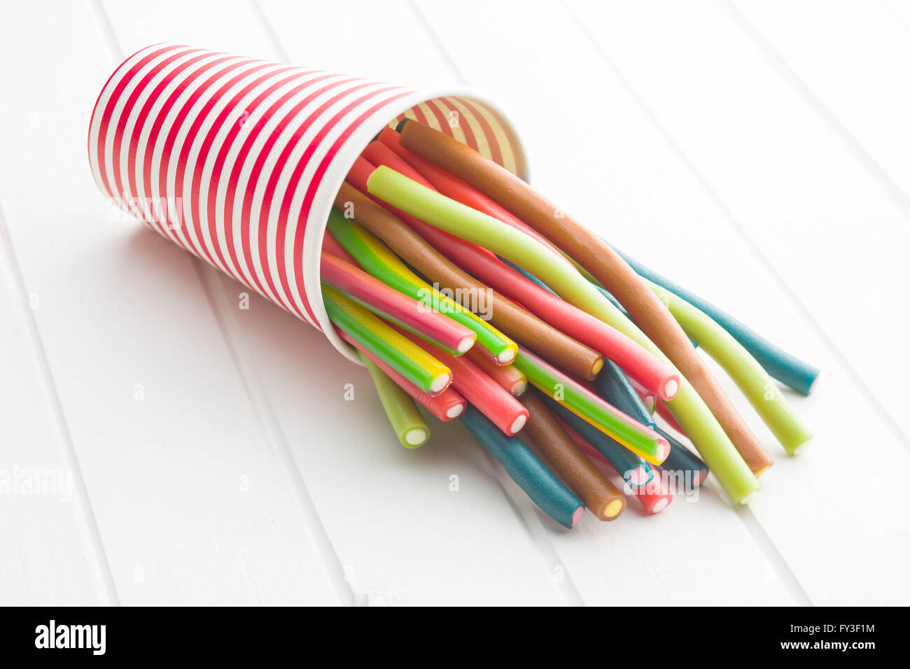 Sweet gummy sticks with different flavor. Tasty candies in paper cup. - Stock Image