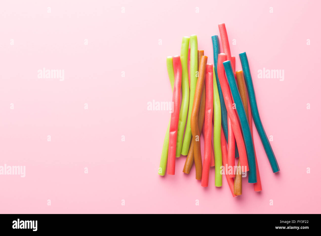 Sweet gummy sticks with different flavor. Top view of tasty candy on pink background. - Stock Image