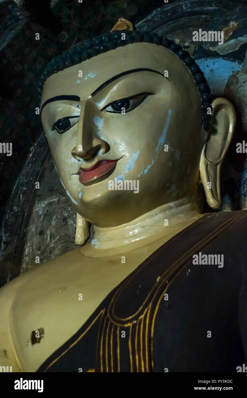 Melancholic ancient traditional Burmese Buddha with scars and scratches in the face Stock Photo