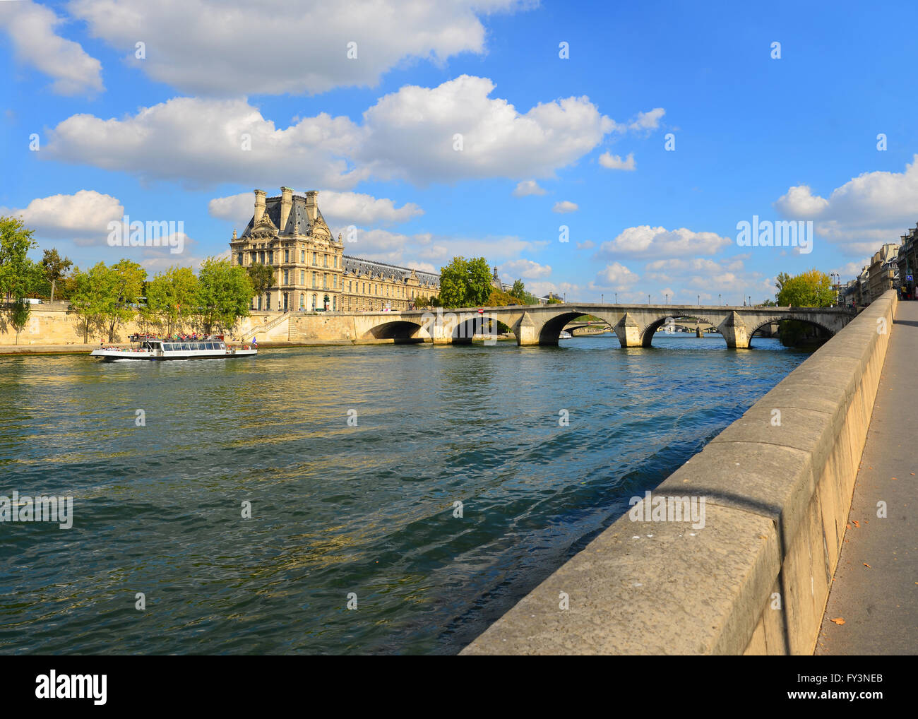 The left bank of the Seine in Paris across from the Tuileries with the Pont Royal the Louvre and a Bateau Mouche. - Stock Image
