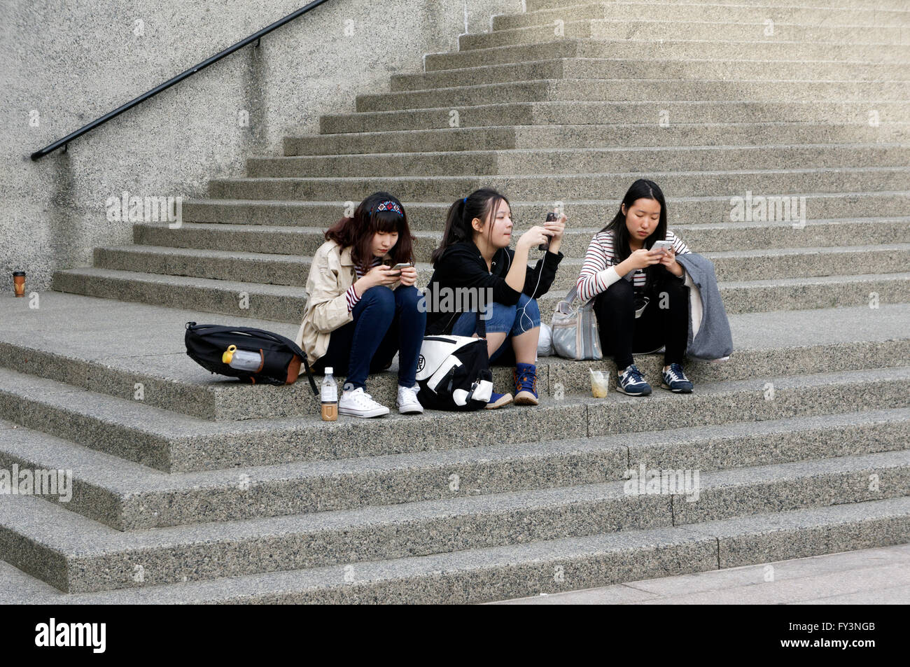 Three young Asian women sitting on concrete steps using their smart phones, Vancouver, BC, Canada - Stock Image