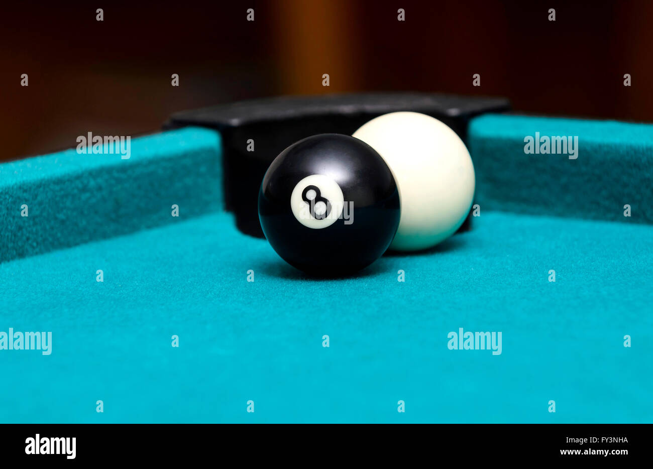 Eight ball and cue ball on pool table - Stock Image