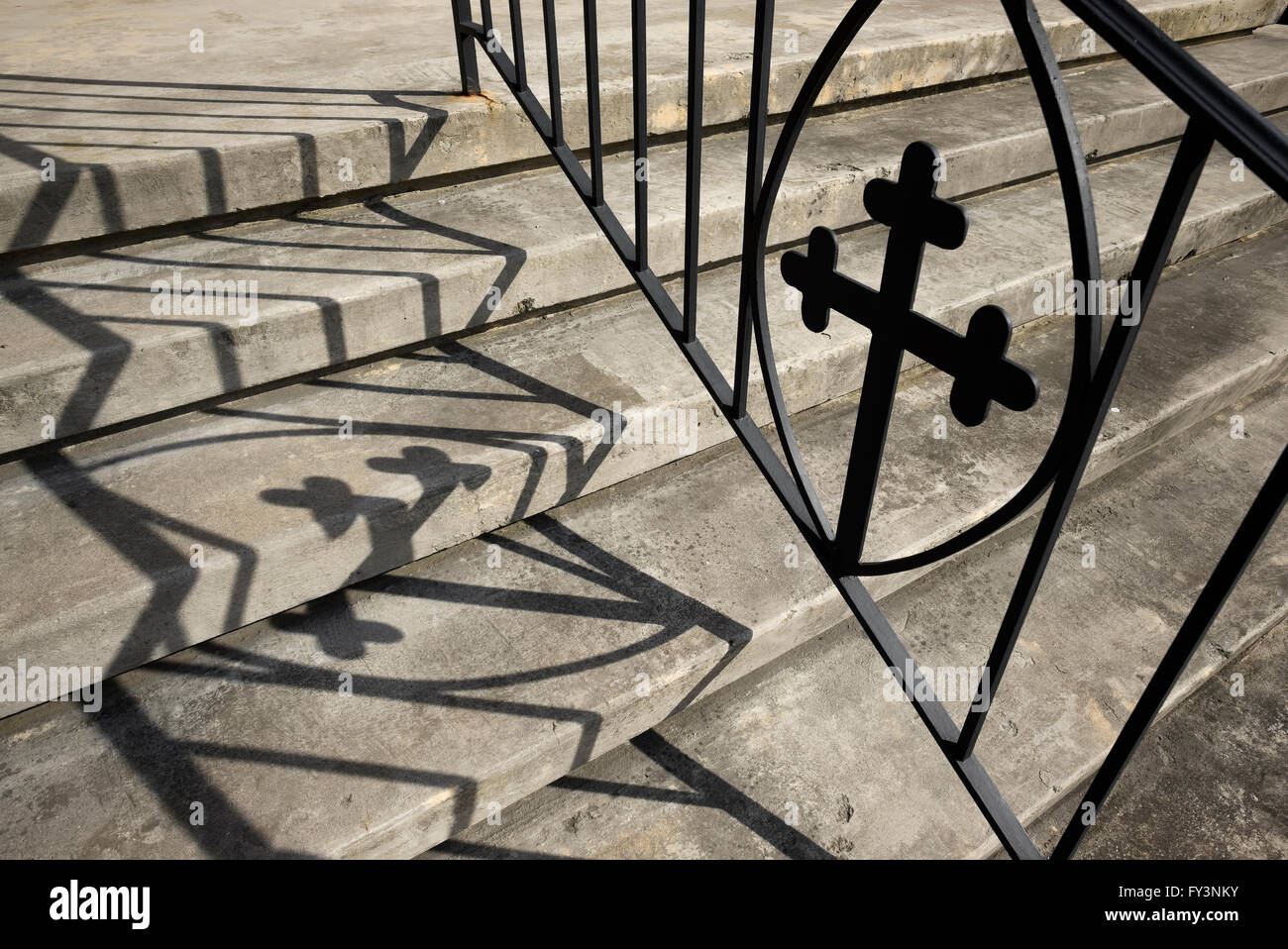 Metal cross in ironwork of handrail on steps of church - Stock Image