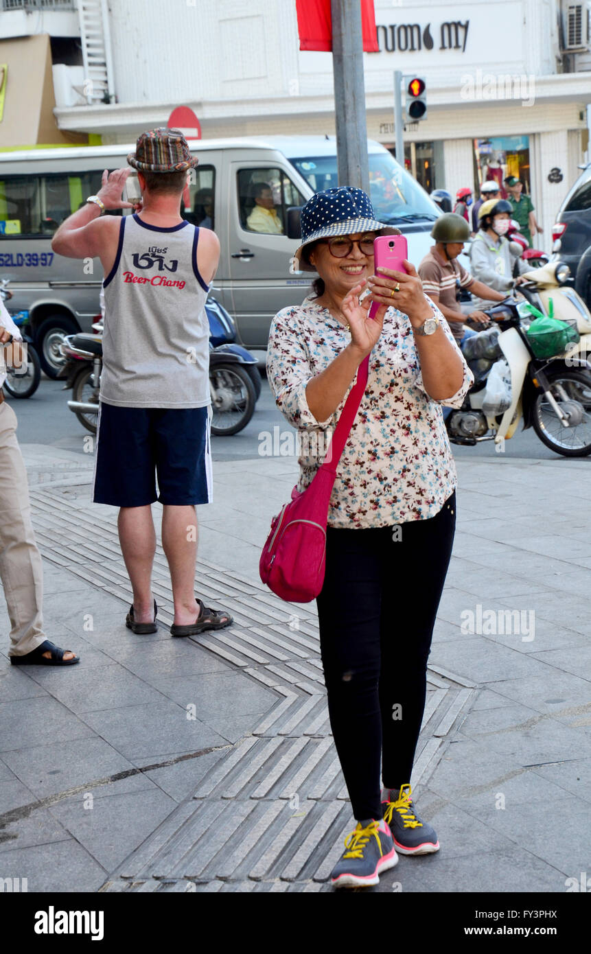 Traveller use smartphone take photo traffic of Saigon city on January 22, 2016 in Ho Chi Minh, Vietnam Stock Photo
