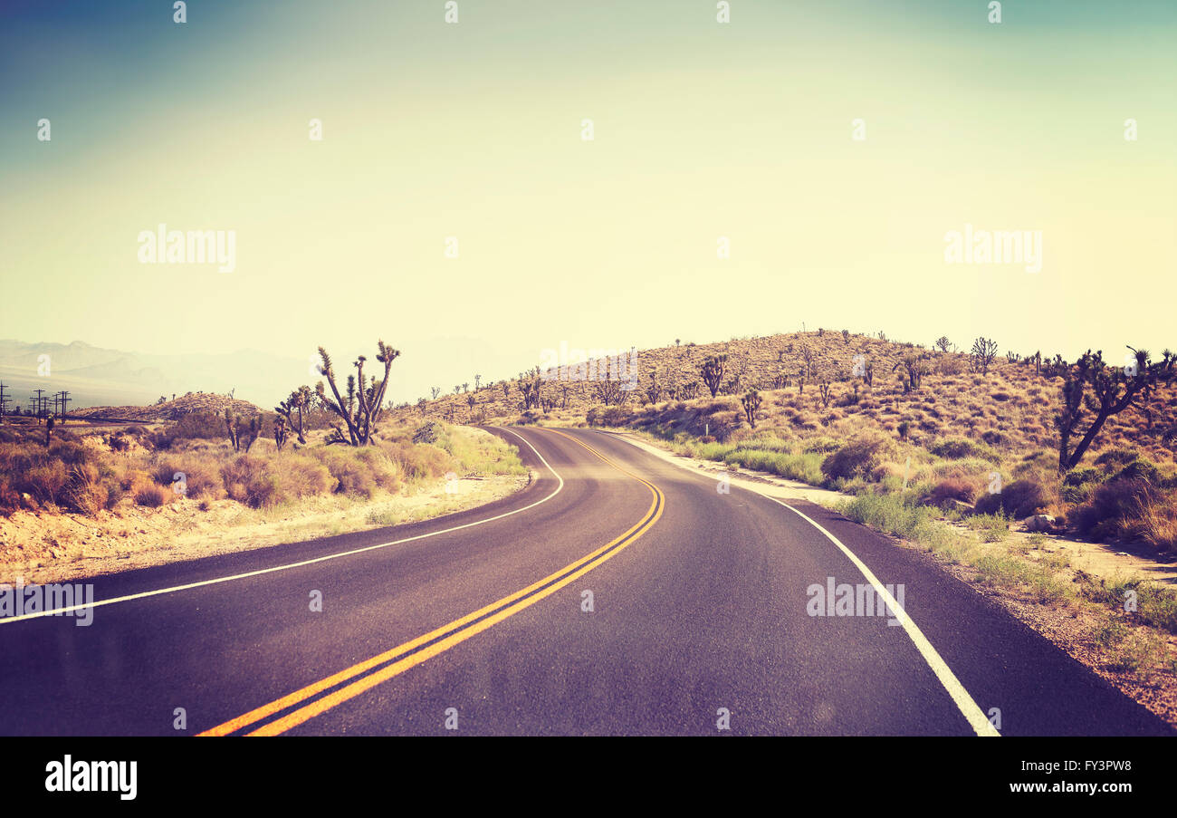 Vintage toned desert road seen through windshield of a moving car. - Stock Image