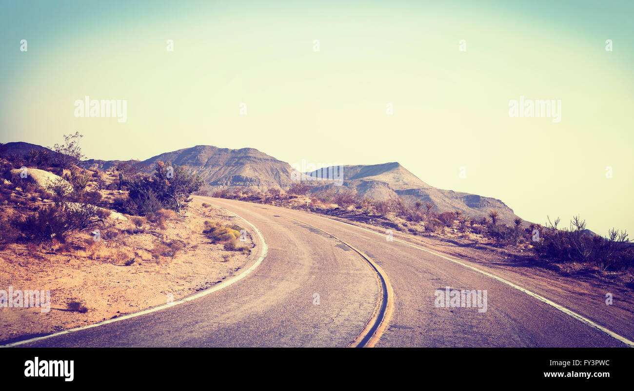 Old film stylized picture of road seen through windshield of a moving car. - Stock Image