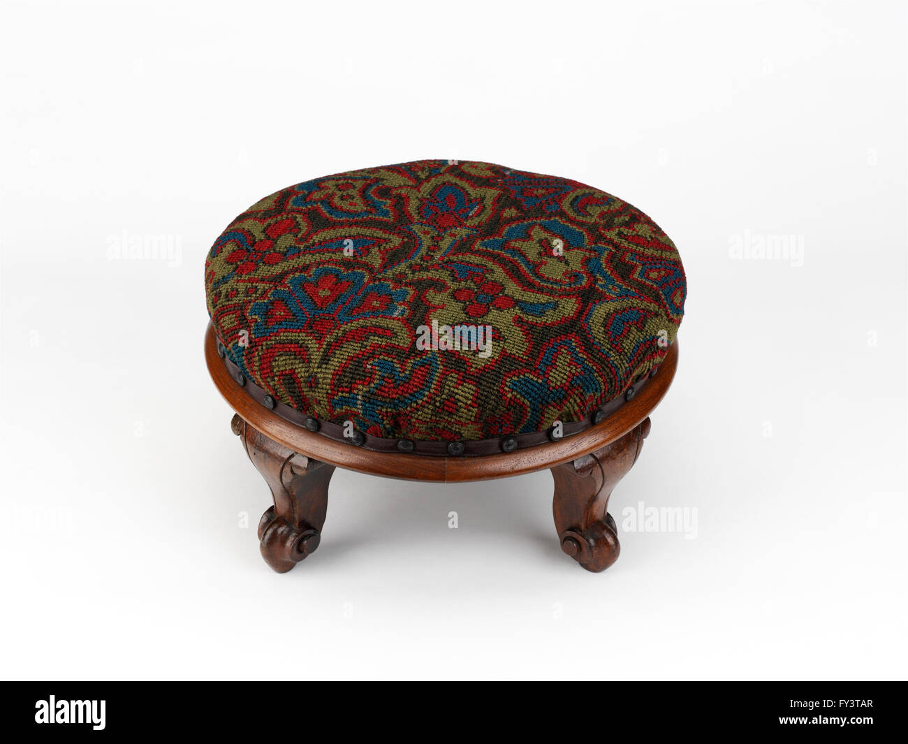 Circular footstool with wooden base and detachable beaded cover - Stock Image