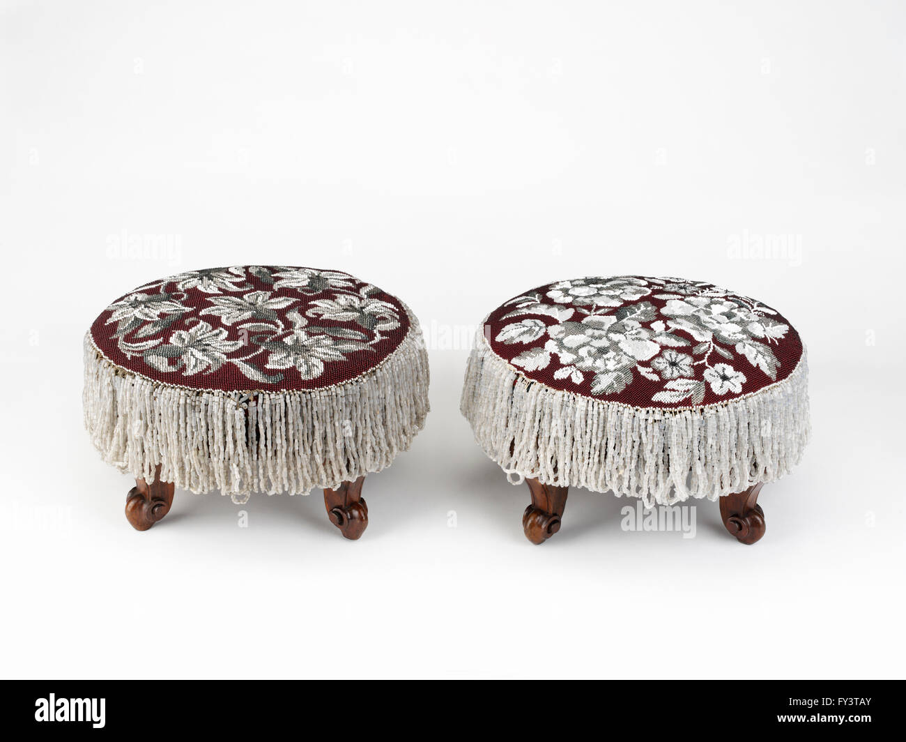 A pair of circular footstools, each with a wooden base and detachable beaded cover - Stock Image