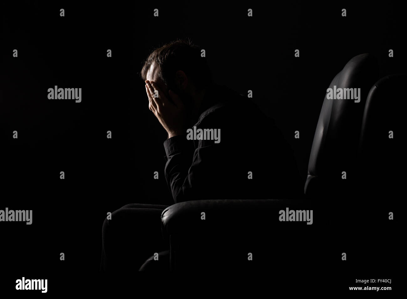 Desperate Man with Hands on His Face Sitting on an Armchair - Stock Image