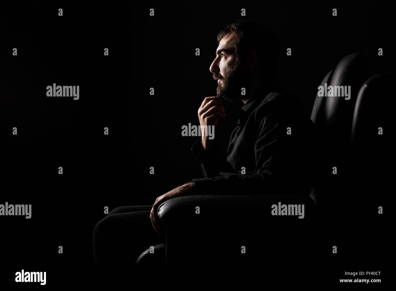Thinking Man with Beard Sittin on an Armchair - Stock Image