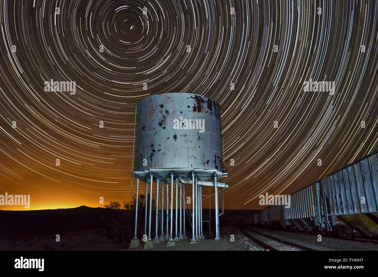 Star trail with old railroad water tower and train cars. Stars form a circular pattern in the night sky over the - Stock Image