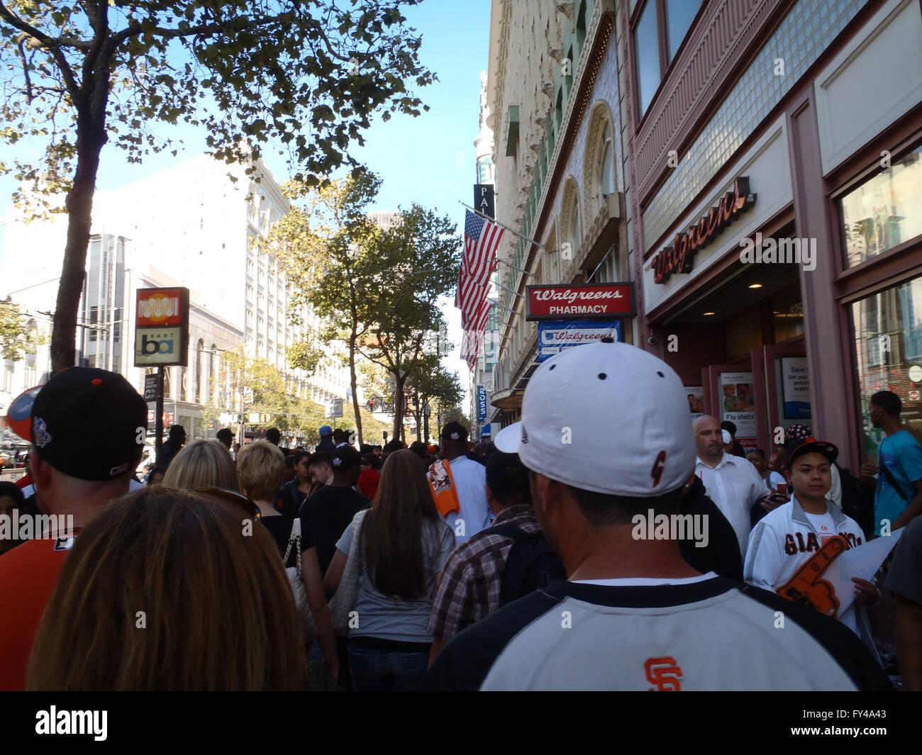 SAN FRANCISCO, CA - NOVEMBER 3: Crowd of Giants fans walk down Market Street by Walgreens, and Muni BART Station - Stock Image