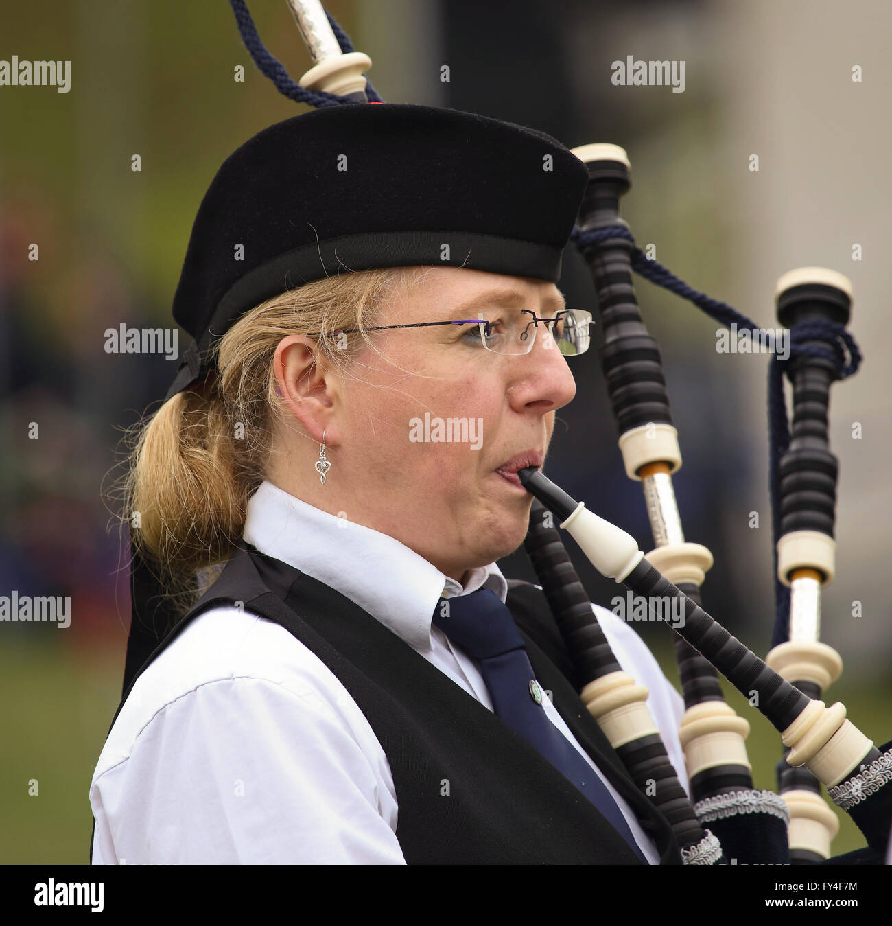 Single female piper from Berlin Thistle Pipes & Drums - Stock Image