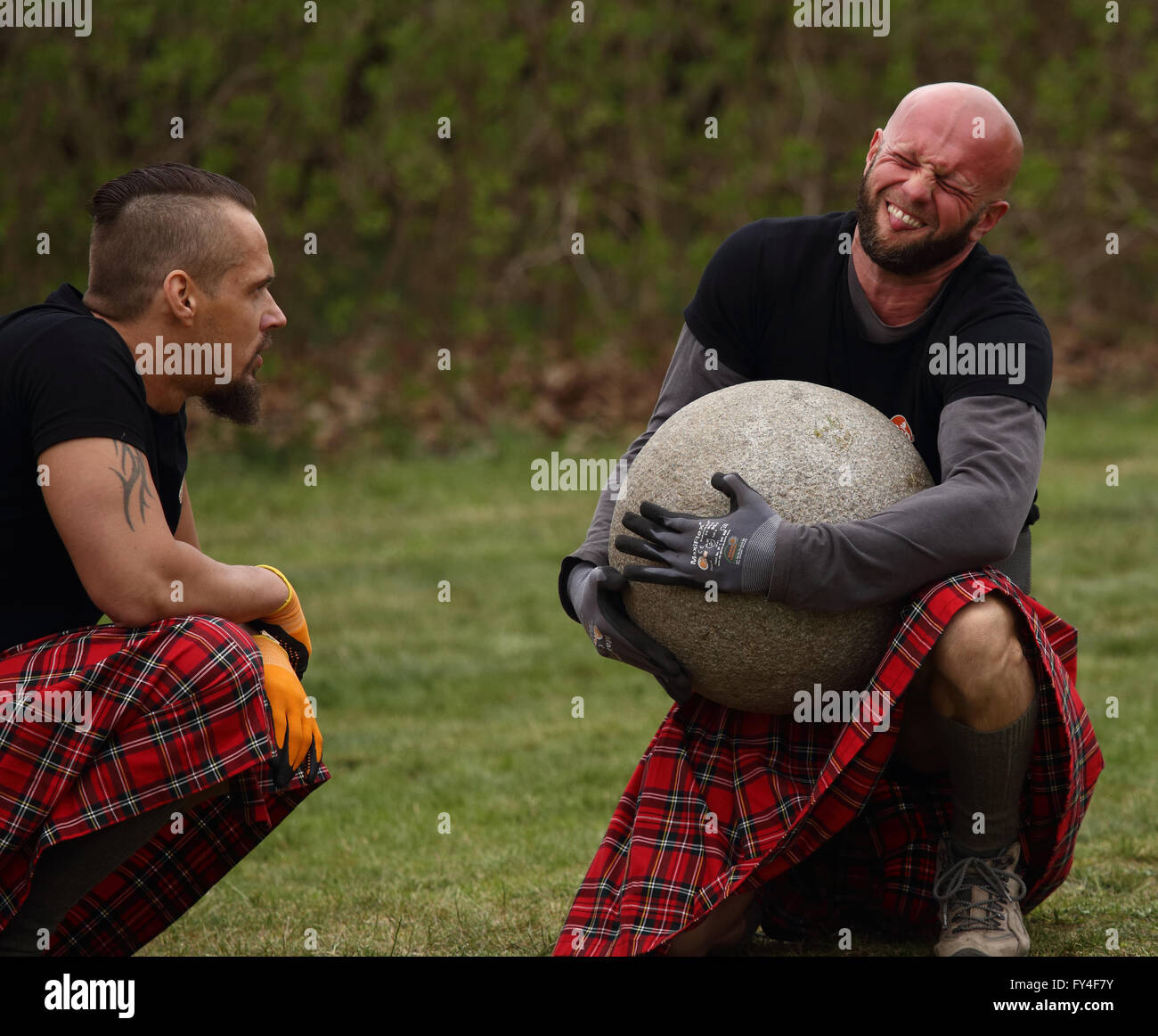 competitor attempting to lift 90 kg stone weight whilst a team mate