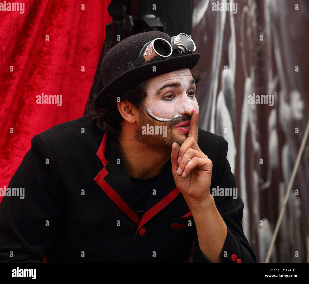 Male clown with bowler hat and goggles with one finger to his lips in a sssshhhh-gesture - Stock Image