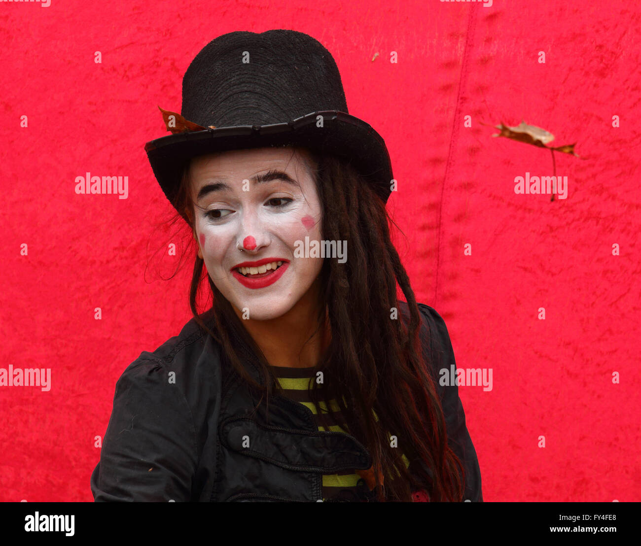 Female clown wearing top hat and make-up against a red background - Stock Image
