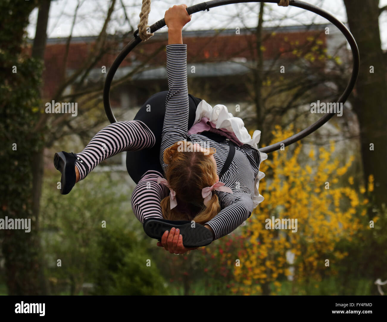 Female acrobat performing outdoor in a large hanging ring - Stock Image