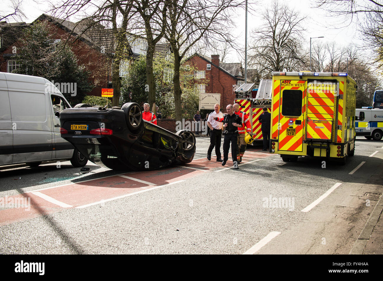 Black Audi car upside down, white transit, labour party banner, ambulance, policeman, firemen, fire engine, police Stock Photo