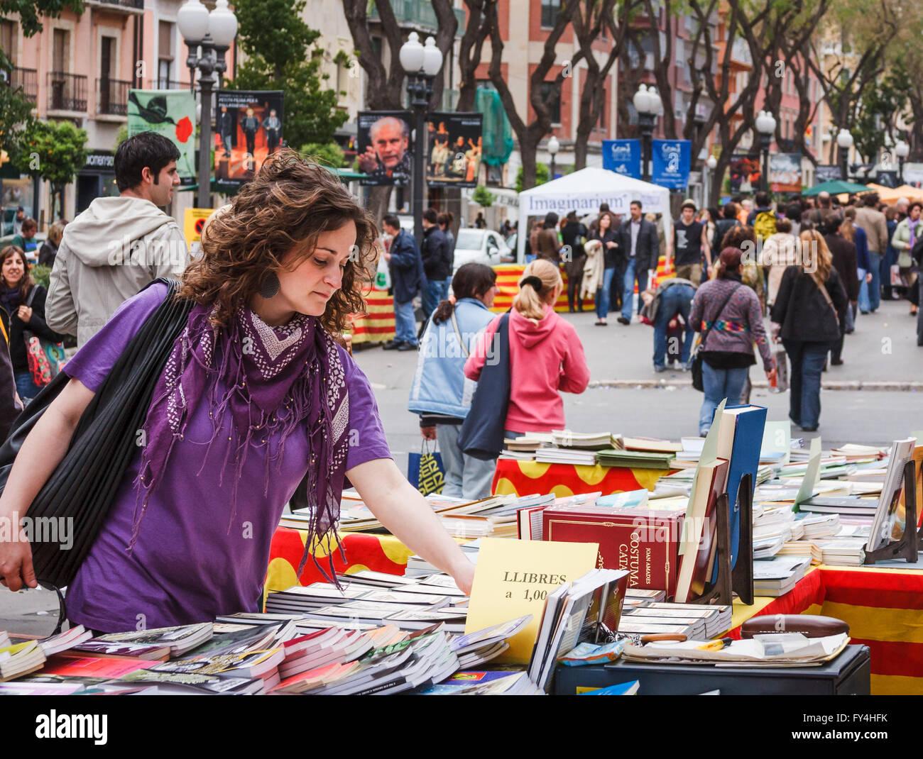 Woman browsing at street bookstall on La Rambla Nova in Tarragona, Catalonia, Spain - 23 April, Sant Jordi day - Stock Image