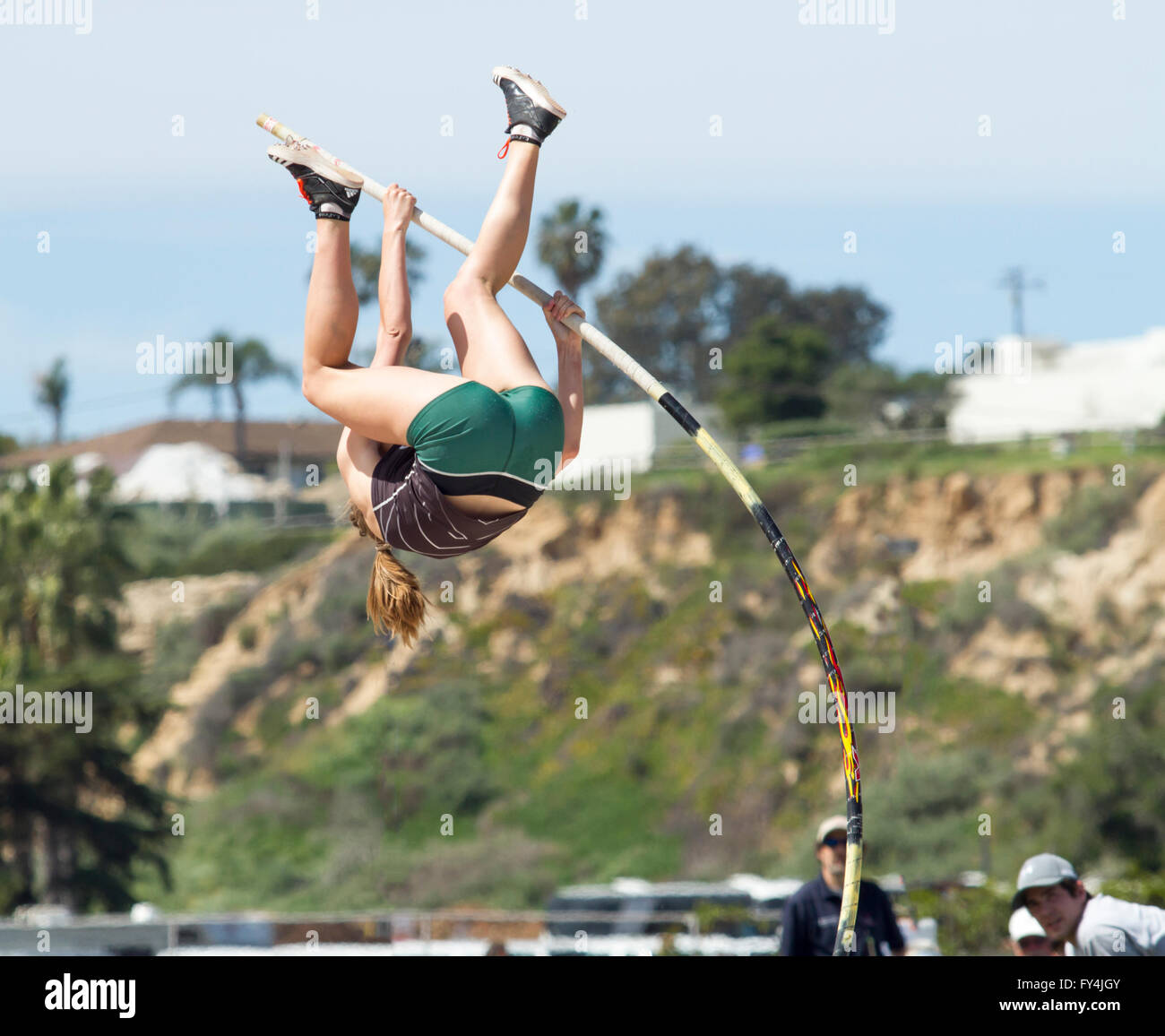 Female pole vaulter building momentum to clear vault bar - Stock Image