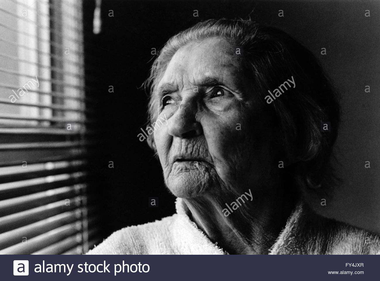 Black and white portrait of a 90 year old woman natural light side lit looking towards window with venetian blind indyfoto