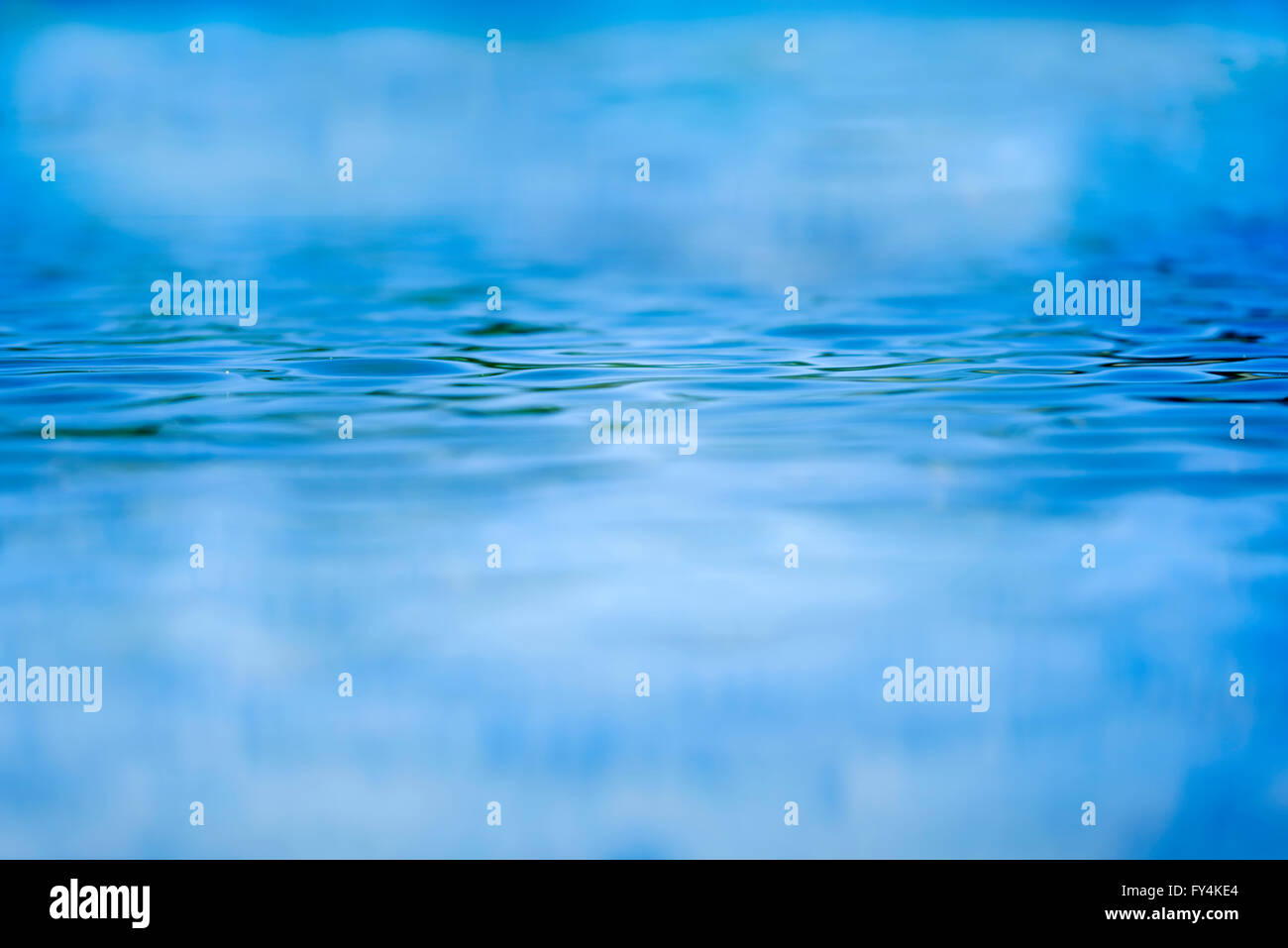Shallow focus looking across blue water with ripples - Stock Image