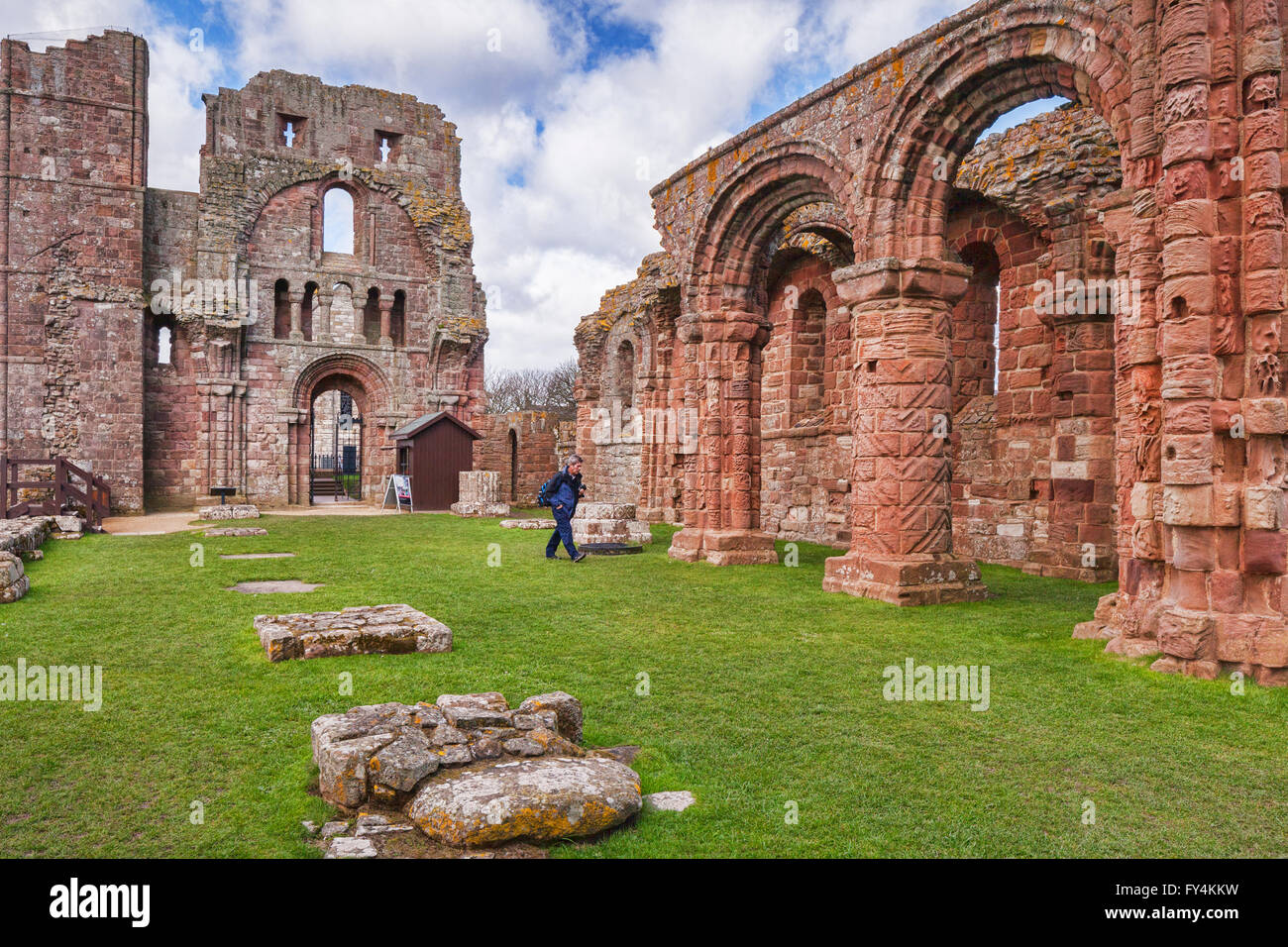 Visitor in the ruins of Lindisfarne Priory, Holy Island, Northumberland, England, UK - Stock Image