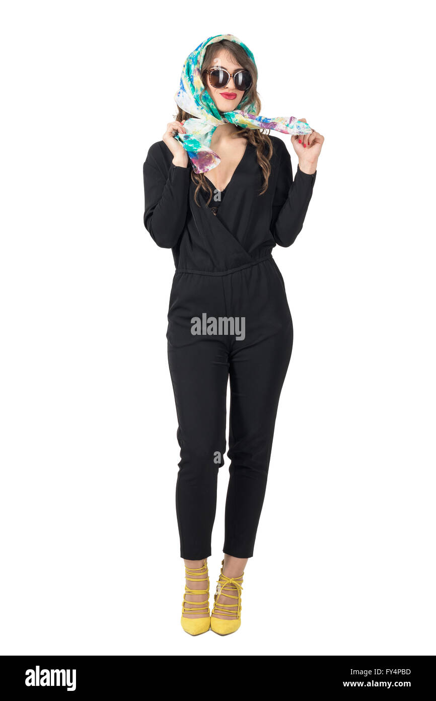1b968e35091a Smiling trendy beauty in jumpsuit wearing sunglasses tying headscarf. Full  body length portrait isolated over