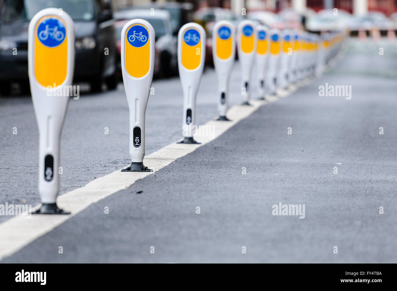 Row of bollards separating a cycle lane from motor vehicles. - Stock Image