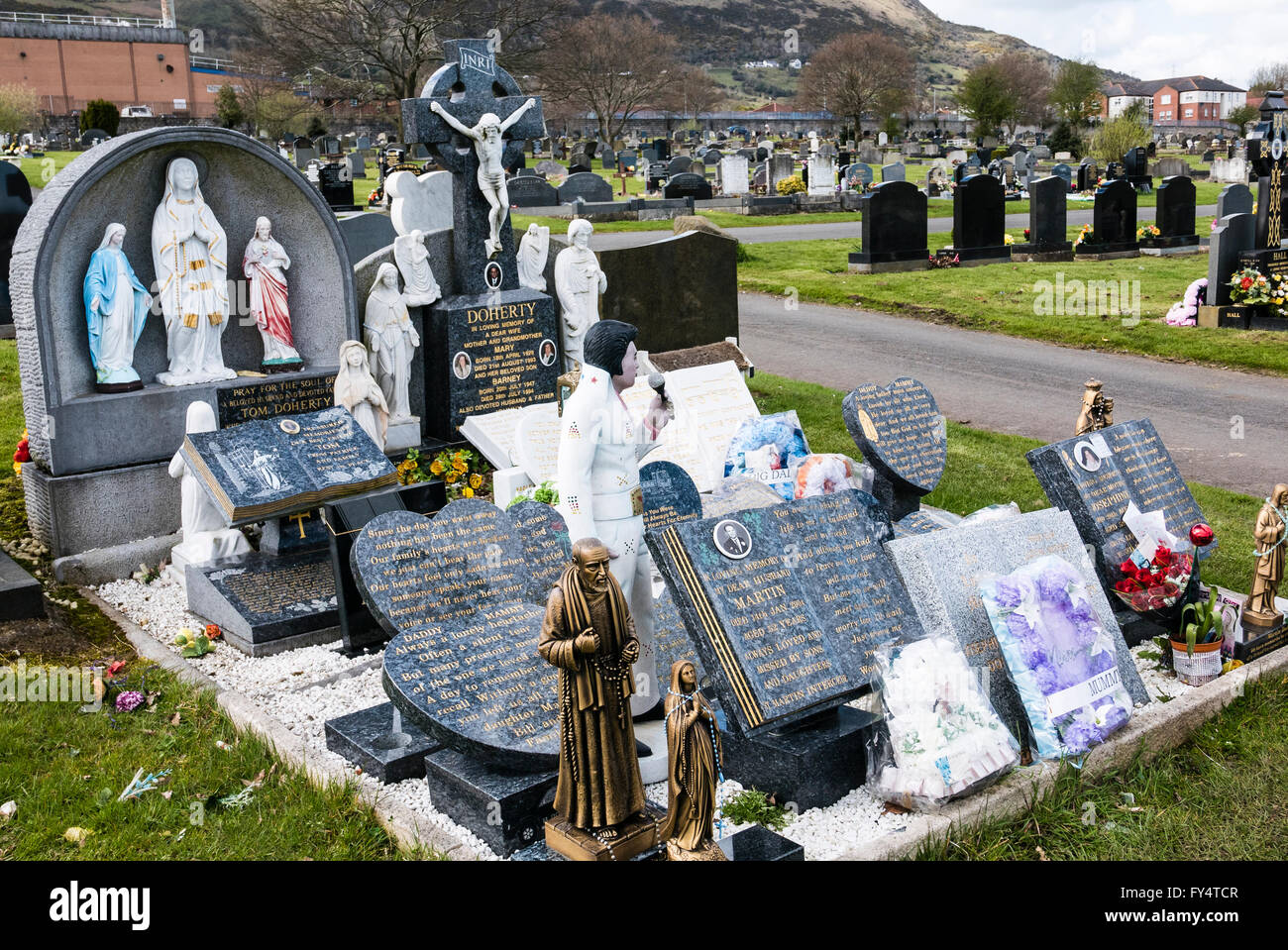 A large number of marble memorial stones on a grave in an Irish graveyard, including a large statue of Elvis Presley. Stock Photo