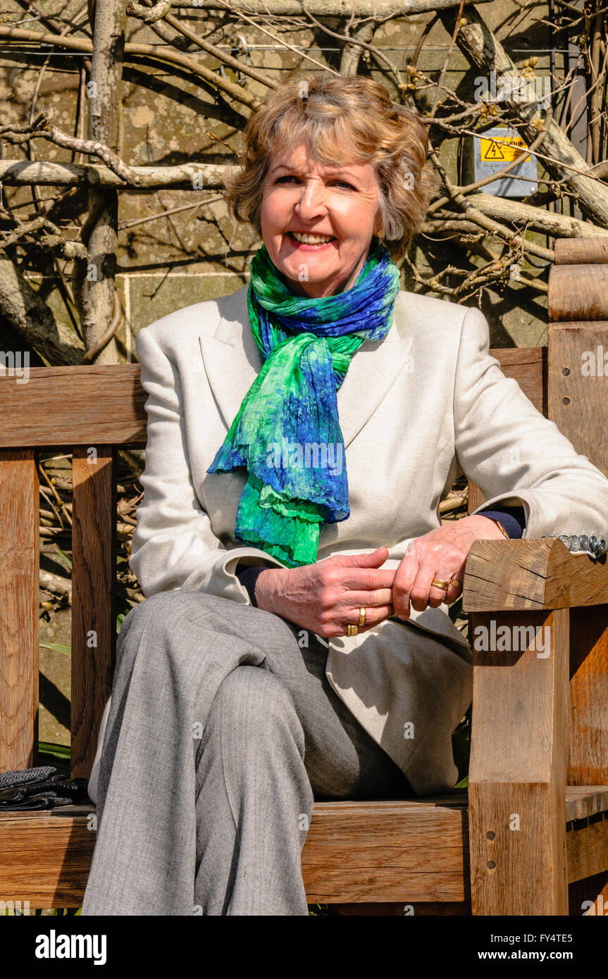 British TV and stage actress Penelope Keith sits on a park bench. - Stock Image