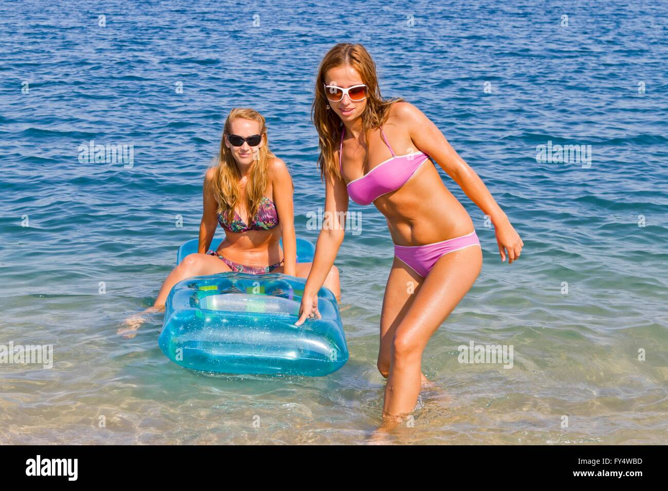 Two attractive girlfriends are having fun on beach pulling inflatable mattress ashore attractive beautiful girl - Stock Image