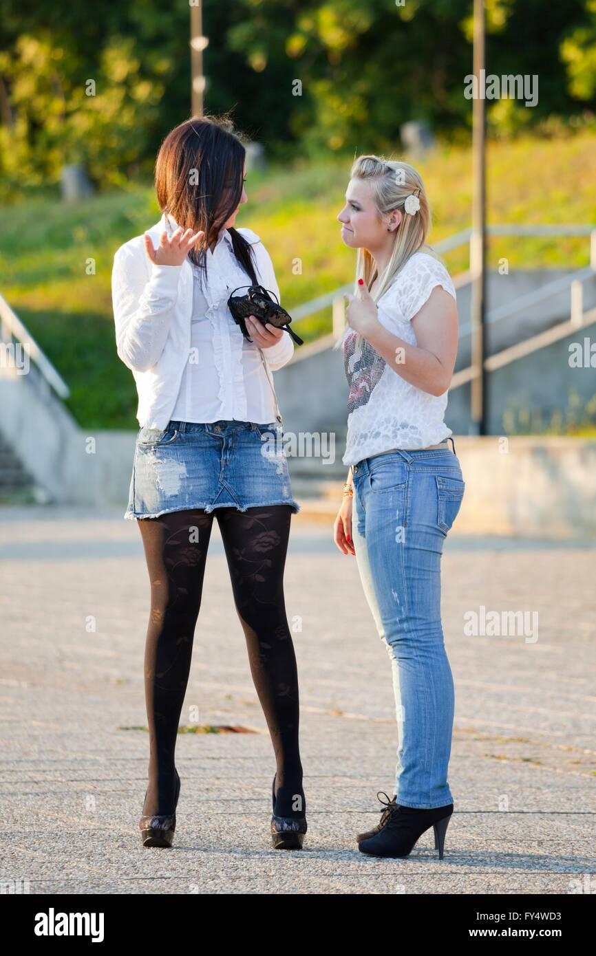 Girlfriends talk on street friendship friend friends outdoors argue arguing talk talking people stiletto pumps apparently - Stock Image