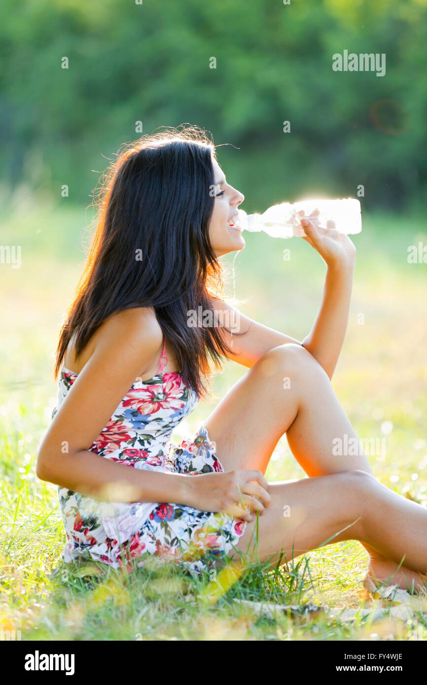 Happy teenager girl is drinking water from a plastic bottle sundress summerdress colorful mini short minidress dress Stock Photo