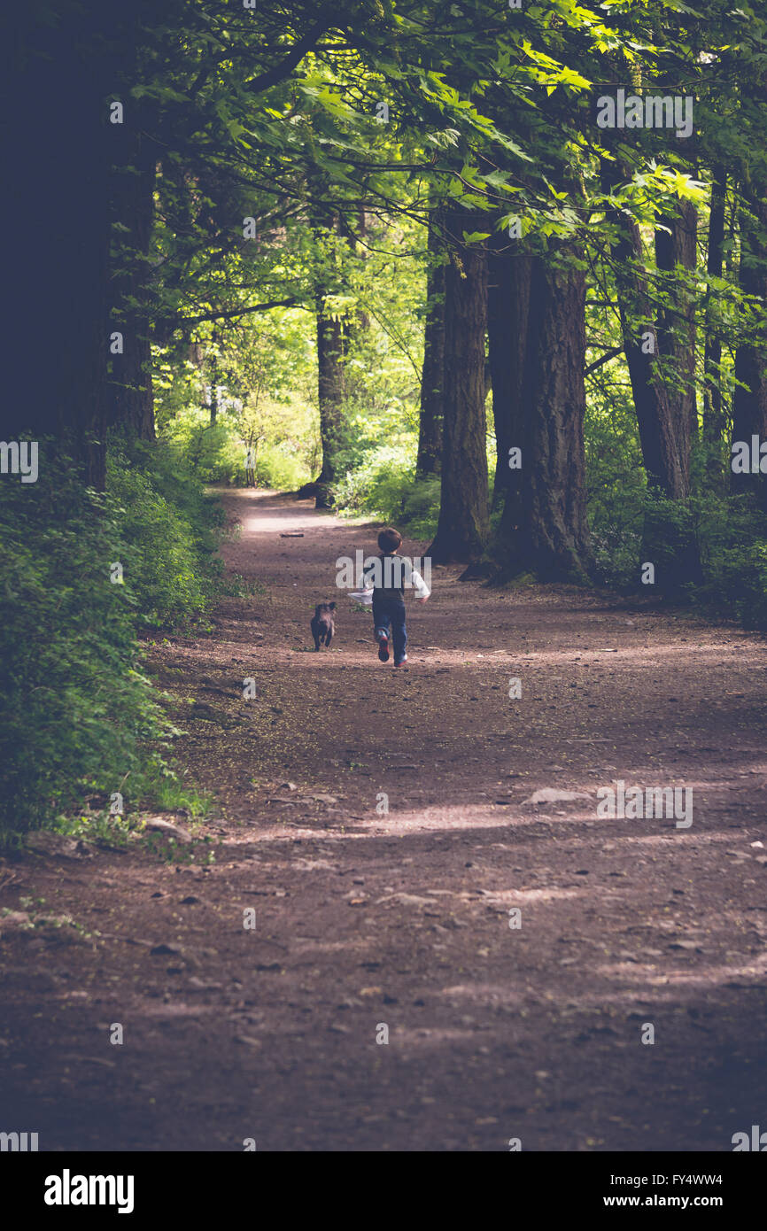 Boy Exploring Forest in Victoria, British Columbia with his dog - Stock Image