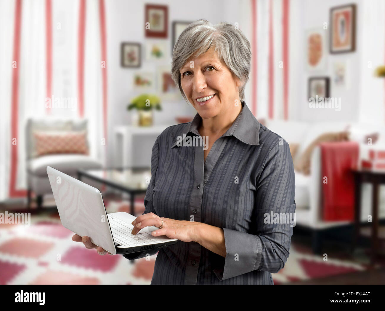 Senior woman using her handheld laptop as she stands in the living room of her house - Stock Image