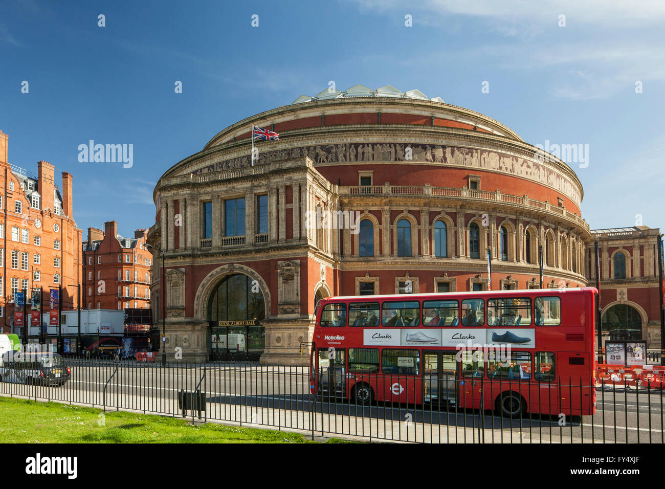 Iconic red double decker bus passes in front of Royal Albert Hall in Kensington, London, England. - Stock Image
