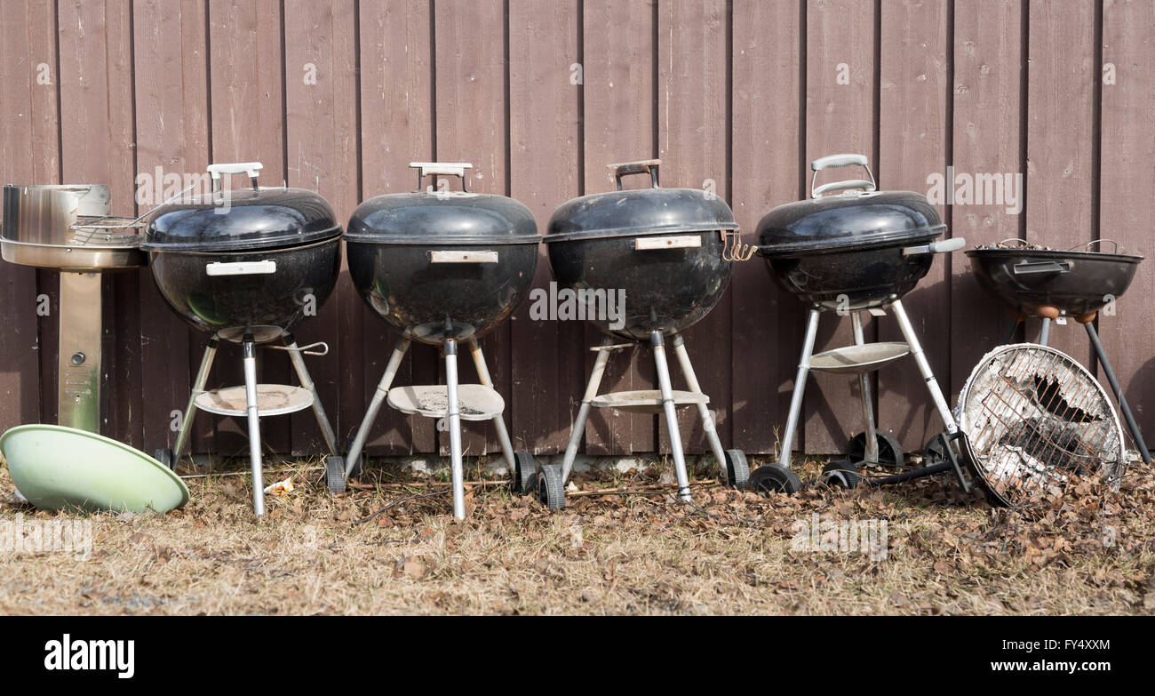 Dome Shaped Barbecue Grills in a row by wall. - Stock Image