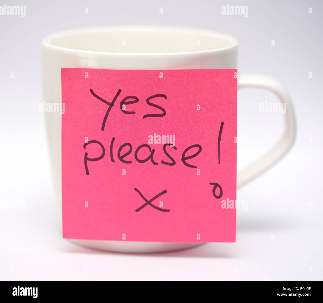 A post it note on a white mug with a hand written message yes please - Stock Image